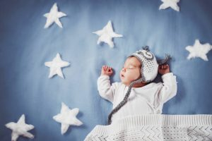 Cute newborn baby girl lying in the bed. 2 month old child in owl hat sleeping on blue blanket with stars.